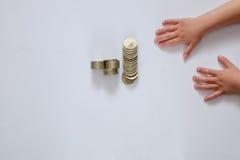 Manos y dinero del ` s de los niños en un fondo blanco Foto de archivo libre de regalías
