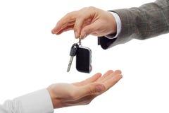 Manos y llave del coche en el fondo blanco Imagen de archivo