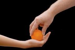 Manos y naranja Fotos de archivo