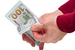 Manos y nuevos cientos billetes de dólar en blanco Imagen de archivo libre de regalías