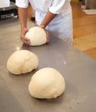Manos y pastas del panadero en el contador Foto de archivo libre de regalías