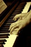 Manos y piano Foto de archivo