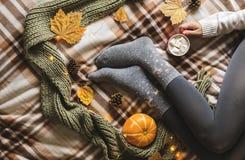 Manos y pies del ` s de las mujeres en el suéter y los calcetines grises acogedores de lana que sostienen la taza de café calient fotos de archivo