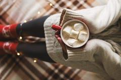 Manos y pies del ` s de las mujeres en el suéter y los calcetines rojos acogedores de lana que sostienen la taza de café caliente foto de archivo libre de regalías