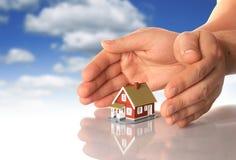 Manos y poca casa. Fotografía de archivo libre de regalías