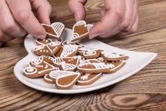 Manos y preparación femeninas de los panes de jengibre adornados dulces para la buena suerte Fotografía de archivo