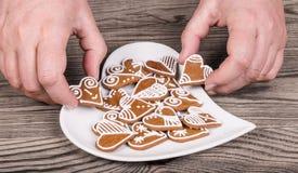 Manos y preparación femeninas de los panes de jengibre dulces para la buena suerte imagenes de archivo