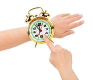 Manos y reloj de alarma como un reloj Foto de archivo
