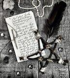 Manoscritto di carta con il testo scritto, il pentagramma e la spoletta della mano sulle plance nel tono nero fotografia stock