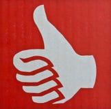 Manosee con los dedos para arriba, como símbolo en fondo rojo Foto de archivo libre de regalías
