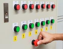 Manosee el tacto con los dedos en el interruptor de paro rojo de emergencia y la tecla de partida verde Imágenes de archivo libres de regalías