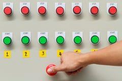 Manosee el tacto con los dedos en el interruptor de paro rojo de emergencia y la tecla de partida verde Fotos de archivo