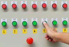Manosee el tacto con los dedos en la tecla de partida verde y el interruptor de paro rojo de emergencia Imagen de archivo libre de regalías