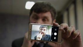 Manovelle occupate dell'impiegato di concetto e esaminare la macchina fotografica del telefono l'uomo d'affari funy seleziona il  archivi video