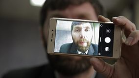 Manovelle occupate dell'impiegato di concetto e esaminare la macchina fotografica del telefono l'uomo d'affari funy seleziona il  stock footage