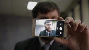 Manovelle occupate dell'impiegato di concetto e esaminare la macchina fotografica del telefono l'uomo d'affari funy seleziona il  video d archivio