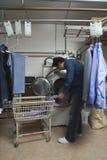 Manpäfyllningskläder i tvagningmaskin på tvätterit Arkivfoton