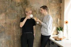 Manpartners som har mat tillsammans Internationella glade par i tillf?llig kl?der som hemma dricker kaffe arkivfoton