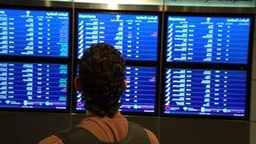 Manpassageraren som ser schemabrädeskärmen på flygplatsterminalen, det internationella flyget, affärsman, reser arkivfilmer