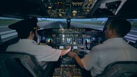 Manpiloten hjälper hans deltagare i utbildning att kontrollera den plana simulatorn Modern inre för passagerareflygplankabin arkivfilmer