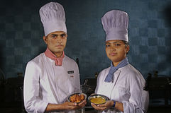 Manpower in hospitality industry. A couple of young man and woman working in hospitality industry in India are showing their food at kitchen of a hotel in India Royalty Free Stock Photo