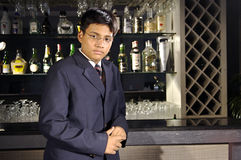 Manpower in hospitality industry. A young man working in hospitality industry in India is standing in front of bar counter of a hotel in India.Quality of Royalty Free Stock Image