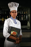Manpower in hospitality industry. A young woman working in hospitality industry in India is standing in front of bar counter of a hotel in India.Quality of Royalty Free Stock Photography