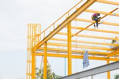 Manpower painting yellow color metal structure on roof top. Manpower painting yellow color metal structure on roof top Stock Photography