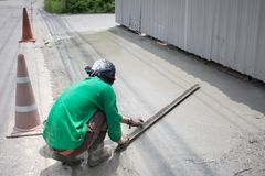 Manpower spreading poured concrete on the road. Royalty Free Stock Image