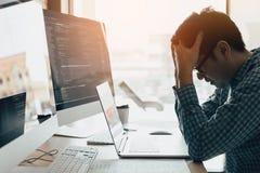 Manprogrammerare belastas och handinnehavhuvudet med huvudvärk på kontoret, medan arbeta analysering på skrivbordet i kod på kont royaltyfri foto