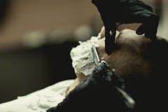 Manrakning en rak rakkniv nära upp med händer royaltyfria bilder