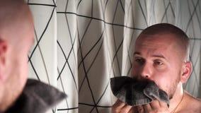 Manrakningar Orakat luta över vasken med handduken på hans huvud, verkar redan klippt och rakat lager videofilmer
