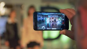 Manrekordvideo på mobiltelefonen från modepassageshow av modeller på catwalk under presentation av den nya samlingen stock video