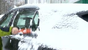 Manrengöringsnö från bilvindrutan efter tungt snowfal stock video