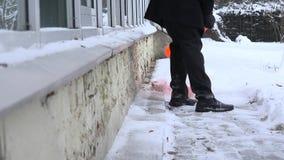 Manrengöringsnö med en skyffel i vintertid 4K lager videofilmer