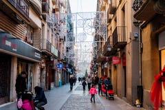 Manresa Spanien - 03 januari 2019: familjer och barn går i upptagna gator under jultid med ljus och garneringar royaltyfri bild