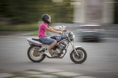 Manridningmotorcykel Den unga grabben i kortslutningar för en rosa T-tröja och grov bomullstvill, med en motorcykelhjälm på hans  Arkivbilder