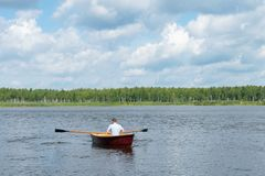 Manrodd i ett träfartyg som svävar på en sjö på en solig dag, aktiv helg, bakre sikt royaltyfri bild