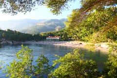 Mansão e praia vistas através das árvores imagem de stock royalty free