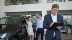 Mansäljaren rymmer biltangenter i hans hand, lyckat avtal, genom att sälja maskinen, stående av representanten i visningslokalen, stock video