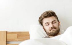 Mansömn på säng Fotografering för Bildbyråer