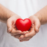 Mans托起了显示红色心脏的手 图库摄影