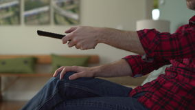 Mans arm as he is changing channels on TV stock footage