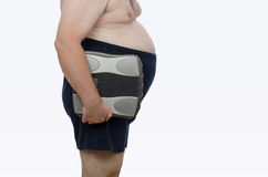 Glutton belly fat with scales. Bellied man posing in profile with weight scales royalty free stock photo