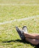 Mans ben som kopplar av på ett gräsfält Royaltyfri Bild