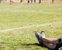 Mans ben som kopplar av på ett gräsfält Fotografering för Bildbyråer