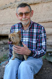 Mans Best Friend. A gentleman in his sixties pauses with his panting dog to sit down and take a rest. The dog is a terrier breed Stock Photos