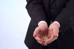 Mans hands with euro coins. Mans in black suit hands with euro coins Royalty Free Stock Images