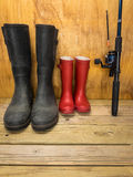 Mans and boys rubber boots with fishing rod. Mans green rubber boots and childs red rubber boots in a shed with fishing rod father and son concept royalty free stock image
