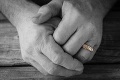 Mans den händer knäppte fast bärande tillsammans vigselringen Royaltyfri Foto